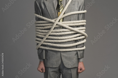 Mid section view of a businessman tied up with ropes