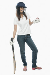 Portrait of a female cricket fan holding bat and a ball