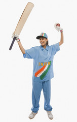 Female cricketer raising bat in celebration