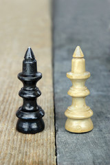 Chess queen figures on a contrast wooden background