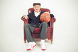 Nice grandfather sitting in a chair holding a basket ball