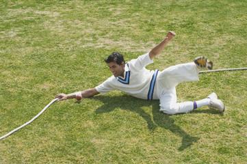Cricket fielder diving to stop a ball near boundary line