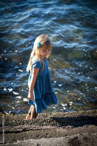 little girl in a blue dress on the sea.