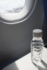Water bottle on seat tray in an airplane, New Delhi, India