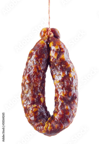 Dry sausage is hanging on hook isolated on white