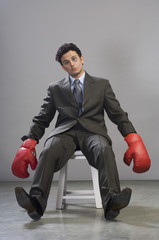 Bruised businessman wearing boxing gloves