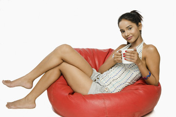 Woman sitting on a bean bag with a cup of coffee