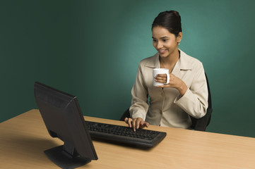 Businesswoman working in an office with a cup of coffee