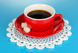 A red cup of strong coffee on blue background