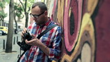 Young hipster taking photo with retro camera by graffiti wall