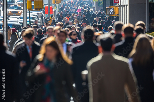 Anonymous crowd of people walking on city street