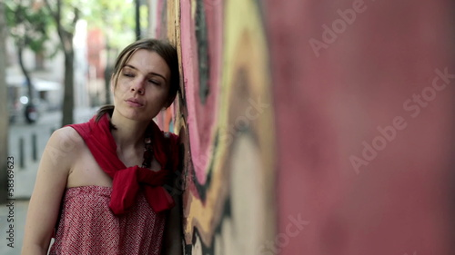 Beautiful sad, pensive woman standing by graffiti wall
