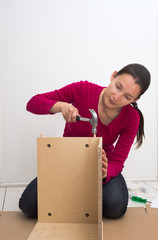 Woman with hammer assembling furniture