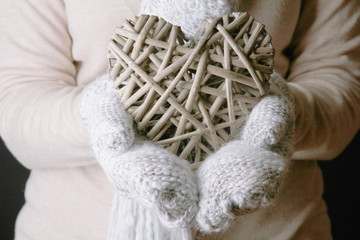Female hands in mittens with heart, close-up