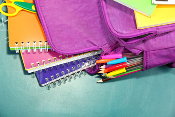 Purple backpack with school supplies on green desk background