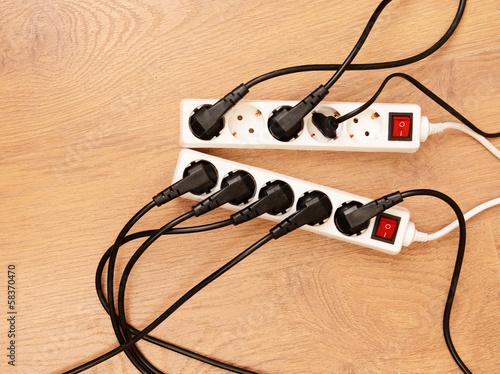 Overloaded power boards, on wooden floor background