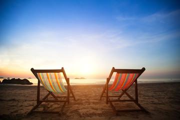 Pair of beach loungers on the deserted coast sea.