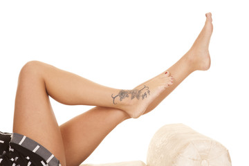 Woman legs crosses tattoo lay foot by calf