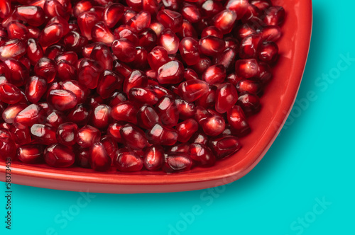 Pomegranate seeds on red heart shaped dish studio shot