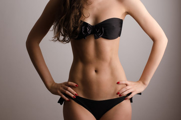 Woman in swimsuit with perfect abs, fit body