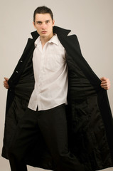 Young businessman in long coat
