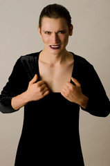 Angry man wearing make up and a black dress