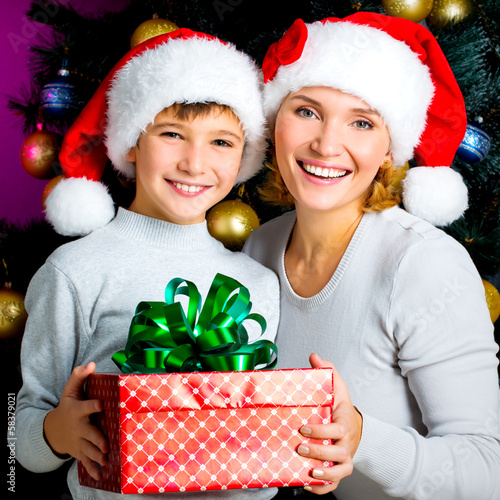 Happy mother with child hold box with gift on the christmas