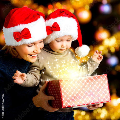 Mother with little child opens the box with gifts on christmas