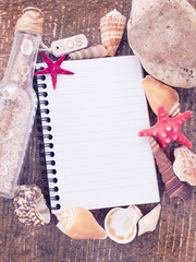 Notebook and seashells on wooden background