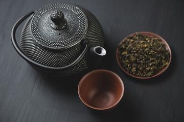 Tetsubin teapot and green tea, dark wooden background