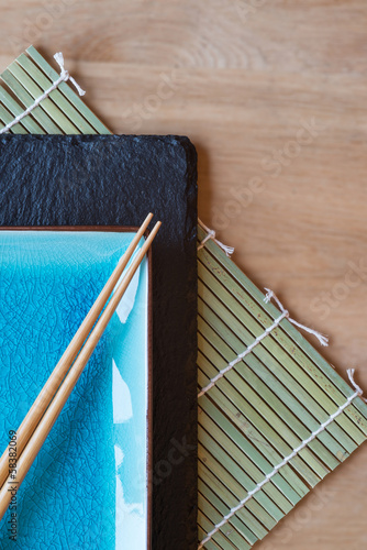 Empty Japanese sushi serving platter with chopsticks