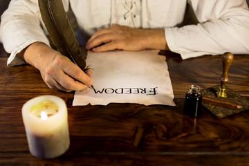 Mann schreibt freedom auf pergament