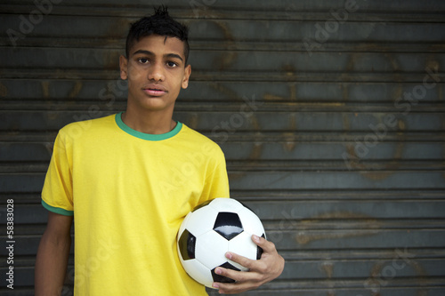 Young Brazilian soccer player holds football