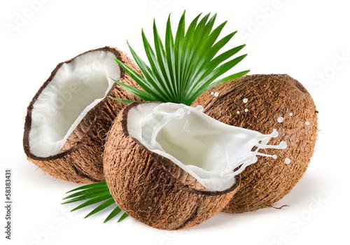 Fototapeta Coconuts with milk splash and leaf on white background