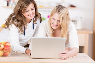 zwei mädchen in der küche schauen auf laptop