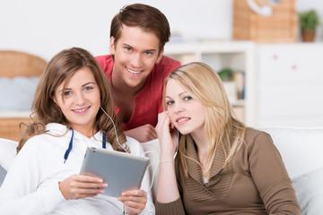 drei junge leute hören musik am tablet-pc