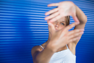 Pretty, young woman making a photo composing/shooting gesture wi
