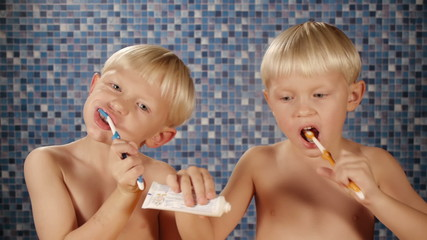 blond twin brothers brushing teeth in bathroom