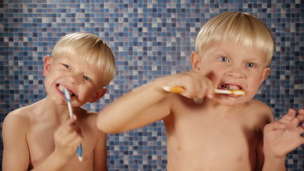 blond twin boys making very funny faces while brushing teeth in