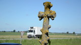 mossy stone cross closeup and car drive risk concept