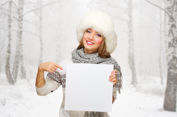 Girl with blank poster at snowy forest
