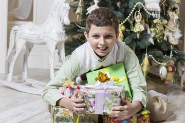Boy hugs his Christmas gifts