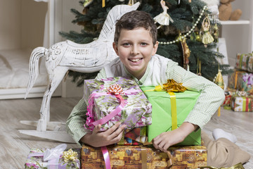 Boy protects a pile of Christmas gifts