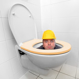 Funny repairman looking from the toilet bowl.