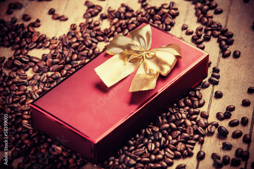 Red gift on wooden table with coffee grain