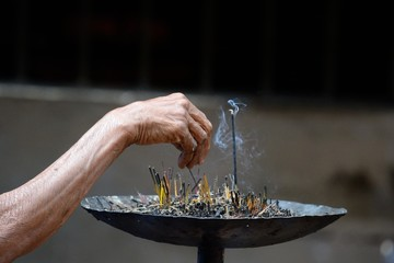 Selective focus on burning incense in an asian temple
