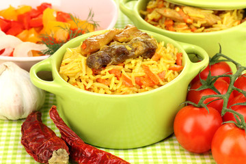 Delicious pilaf with vegetables on tablecloth background