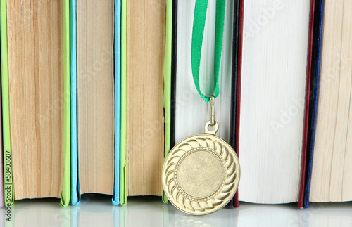 Medal for achievement in education with books close up