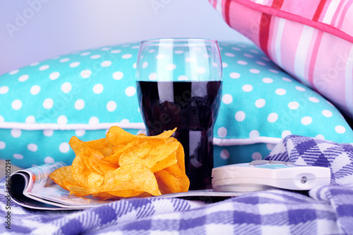 Chips in bowl, cola and TV remote on plaid on pillows