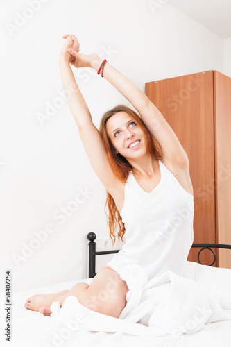 Red-haired woman stretching on white pillow in bed at home